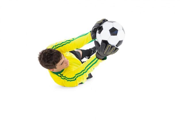 Portiere in giallo tenendo palla