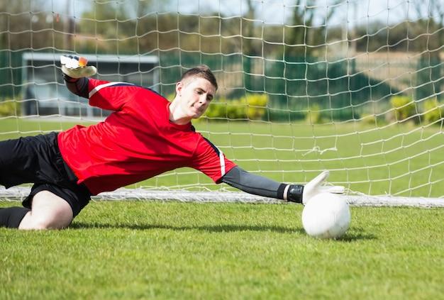 Portiere in rosso che salva un gol durante una partita