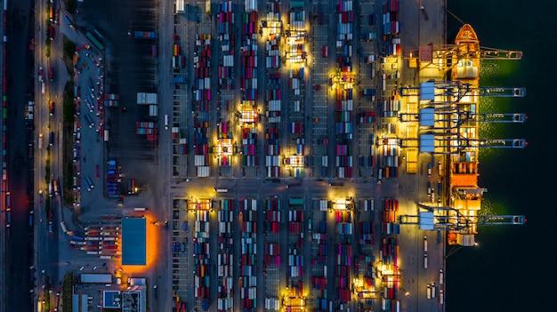 Porto marittimo industriale che lavora alla notte con la nave porta-container che lavora alla notte, nave porta-container di vista aerea che carica e che scarica alla notte.