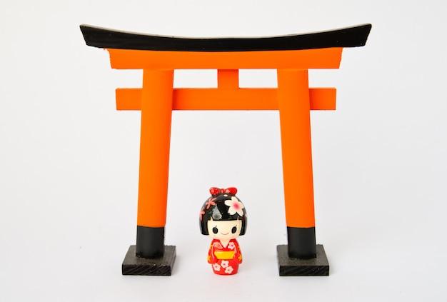 Portone di torii con le bambole giapponesi su fondo bianco