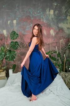 Portraita giovane donna bruna, che indossa un abito blu