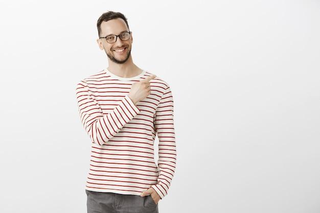 Portrat di fiero ragazzo fiducioso in occhiali, tenendo la mano in tasca e indicando l'angolo in alto a destra con un ampio sorriso sul viso
