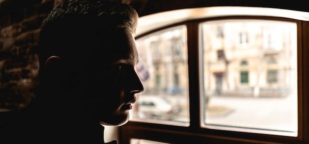 Portriat o silhouette di giovane uomo seduto davanti alla finestra