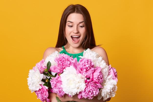Portrtait di bella sorpresa giovane donna romantica, in posa con la bocca aperta, sorridente ragazza con bouquet di fiori di peonia bianca e rosa