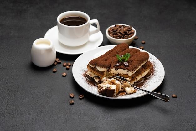 Porzione di dessert tiramisù classico e tazza di caffè espresso fresco su fondo o tavola concreti
