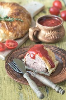 Porzione di manzo wellington con salsa di pomodoro