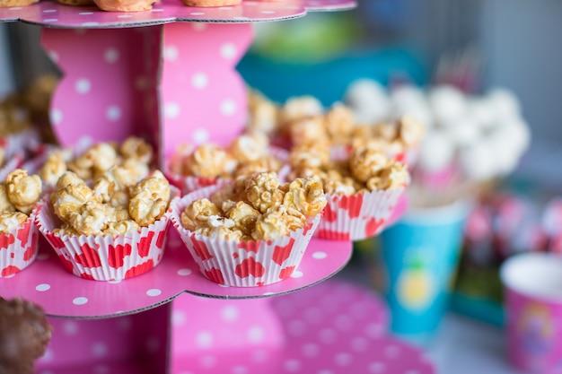 Porzione di popcorn sulla festa dei bambini sul tavolo da dessert dolce