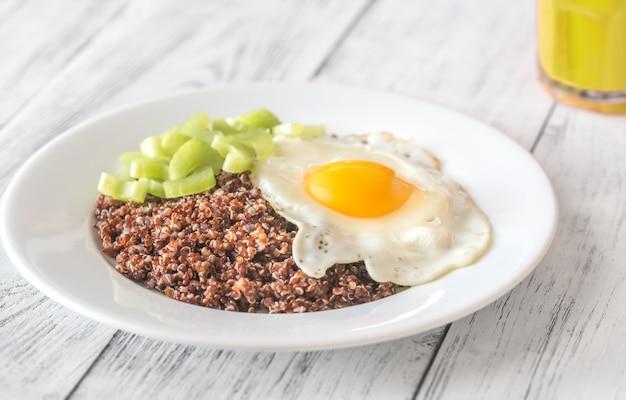 Porzione di quinoa rossa con uovo fritto e sedano