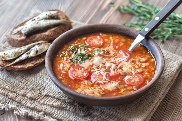 Porzione di zuppa di pomodoro con lenticchie verdi e toast