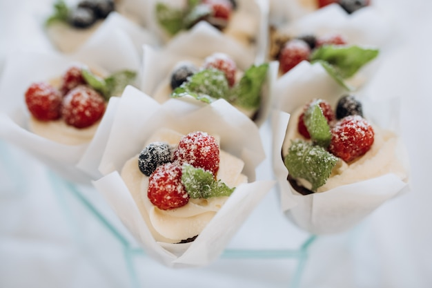Porzioni di dessert decorate con panna e frutti di bosco