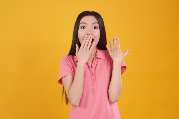Posa asiatica della ragazza eccitata su fondo giallo.