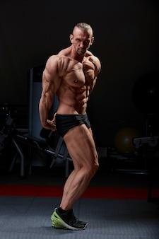 Posa atletica dell'uomo. foto di uomo con fisico perfetto su sfondo nero. forza e motivazione