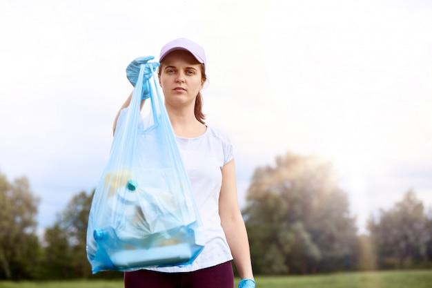Posa d'uso della maglietta e del berretto da baseball della giovane ragazza caucasica all'aperto con la borsa di immondizia, si preoccupa per l'ambiente, stando con il cielo e gli alberi
