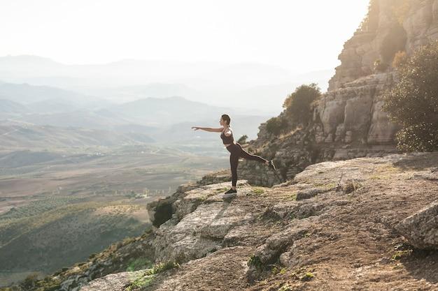 Posa dell'equilibrio di yoga di vista frontale sulla montagna
