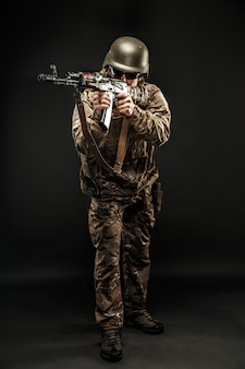 Posa dell'uomo armato di servizio mirando