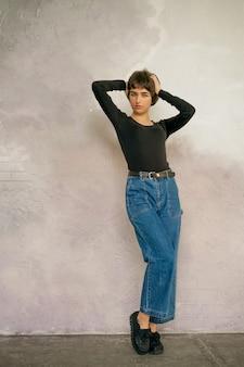 Posa della donna dei pantaloni a vita bassa