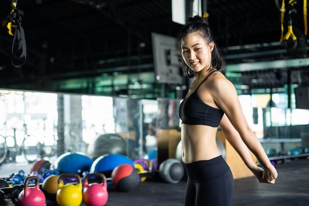 Posa della donna di forma fisica a pratica di yoga della palestra.