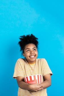 Posa della donna felice mentre tenendo il secchio del popcorn