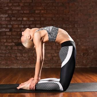 Posa di ginnastica della donna della foto a figura intera