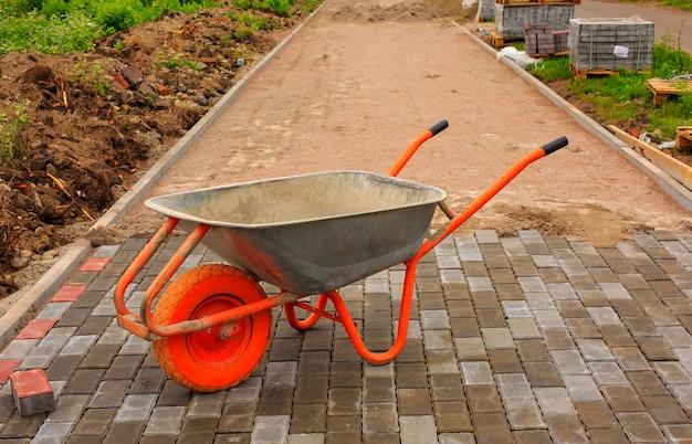Posa di lastre per pavimentazione. riparazione del marciapiede. carriola.