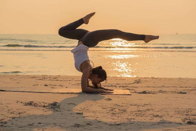 Posa di pratica di yoga della giovane donna in buona salute di yoga sulla spiaggia all'alba