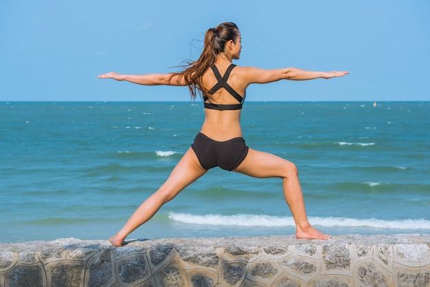 Posa di pratica di yoga della giovane donna in buona salute di yoga sulla spiaggia di mattina