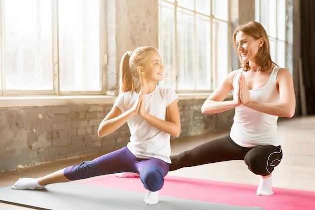 Posa di yoga di pratica della figlia e della madre