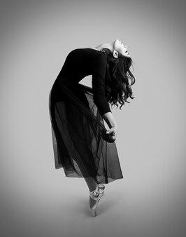 Posa femminile acrobatica in vestito di pizzo