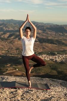Posa femminile di yoga con equilibrio