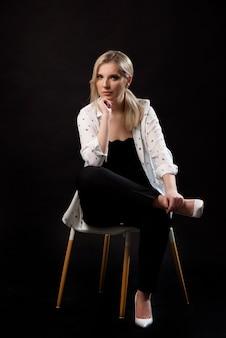Posa giovane della donna di affari isolata sopra il fondo nero della parete che si siede su una sedia.