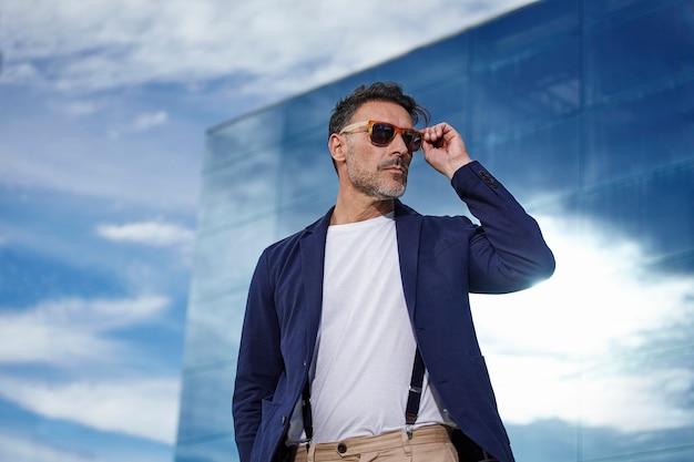Posa matura con giacca blu e occhiali da sole