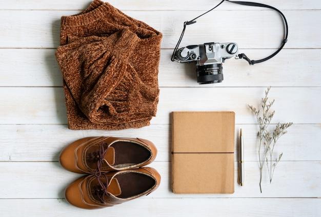 Posa piatta con abbigliamento caldo e confortevole per la stagione fredda. autunno comodo, vestiti di inverno che comperano, vendita, stile nel concetto di colori di tono della terra, vista superiore