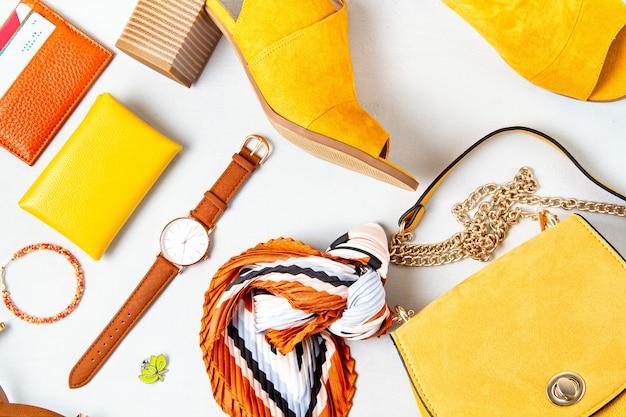 Posa piatta con accessori moda donna nei colori gialli.