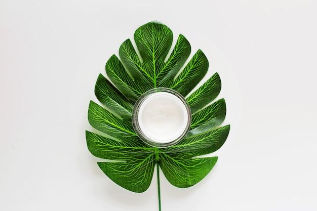 Posa piatta con cosmetici biologici naturali: crema con foglia verde. cura della pelle, cosmetologia, concetto di dermatologia.