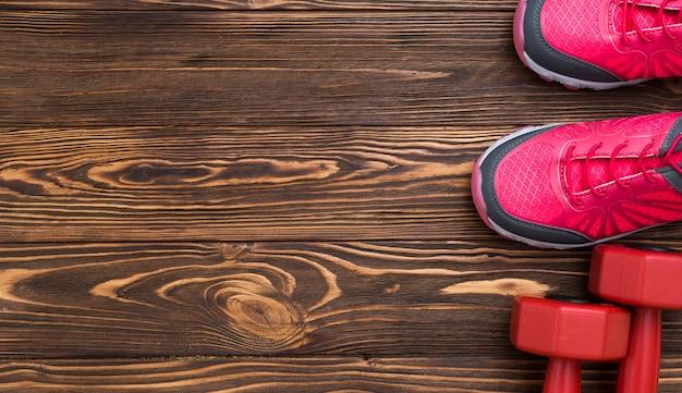 Posa piatta di pesi con scarpe da ginnastica e copia spazio