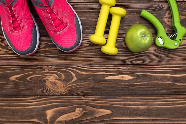 Posa piatta di pesi con scarpe da ginnastica e mela
