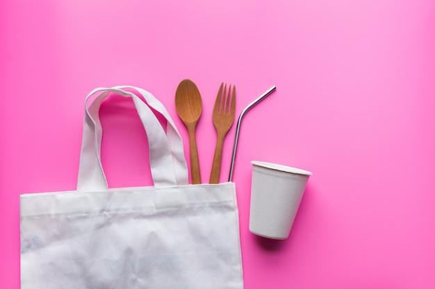 Posa piatta di prodotti sostenibili, spowooden e paglia inossidabile in sacchetto di stoffa sul rosa
