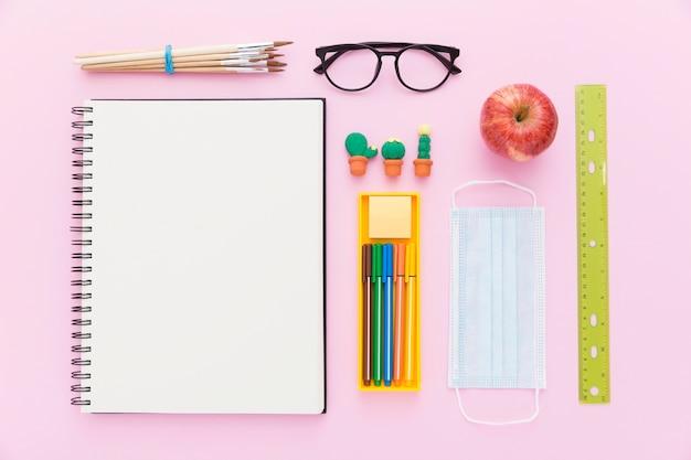 Posa piatta di ritorno a materiale scolastico con quaderno e matite