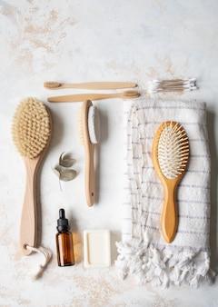 Posa piatta di spazzola per il corpo, asciugamano di cotone bianco, pomice, spazzolino da denti in bambù, olio aromatico e un pezzo di sapone. concetto di rifiuti zero. set da bagno ecologico.