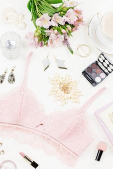 Posa piatta femminile con accessori moda donna, lingerie, gioielli, cosmetici, caffè e fiori. vista dall'alto