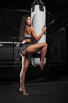 Posa sexy dell'atleta di bello bikini di forma fisica con un punching ball