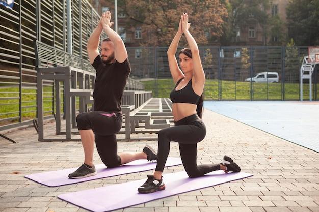 Posa yoga sul tappetino con giovani sportivi