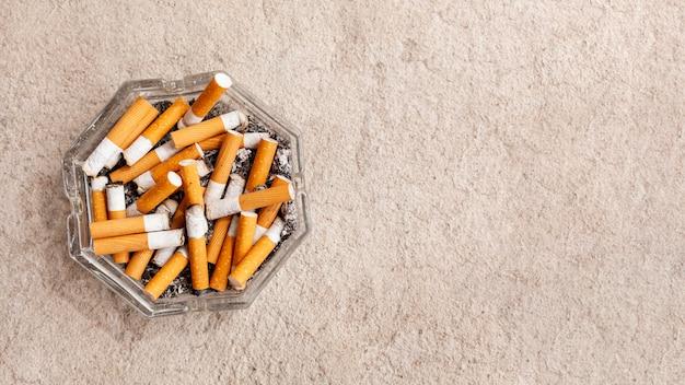 Posacenere copia-spazio con sigarette