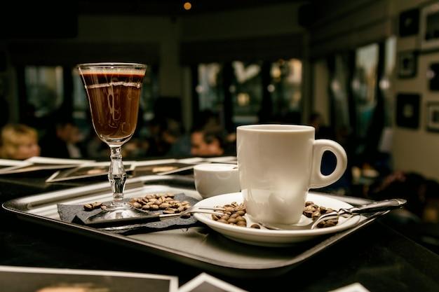 Posate con bicchieri di caffè e chicchi di caffè in serata caffè