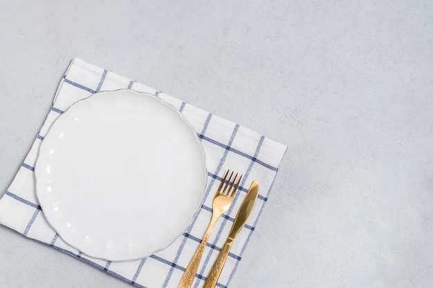 Posate con piatto vuoto bianco e coltello dorato e forchetta sul tavolo neutro