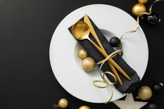 Posate d'oro servite sul piatto per la cena di natale