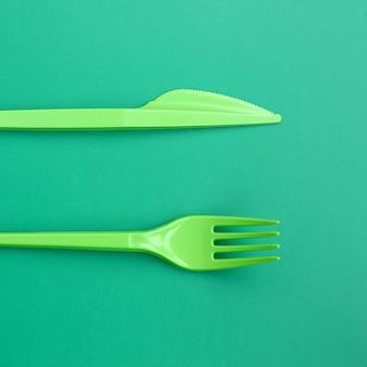 Posate di plastica usa e getta verde. la forcella e la lama di plastica si trovano su una superficie verde del fondo