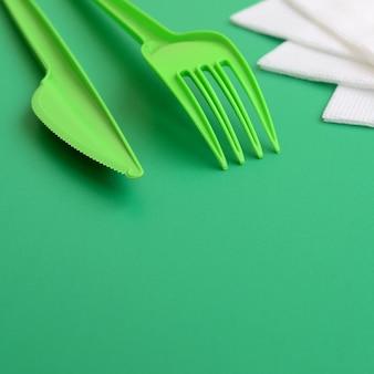 Posate di plastica usa e getta verde. la forchetta e il coltello di plastica si trovano su una superficie di fondo verde accanto ai tovaglioli