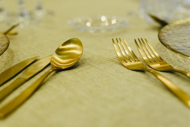 Posate dorate di lusso per occasioni speciali come il natale su un tavolo con una tovaglia rustica.