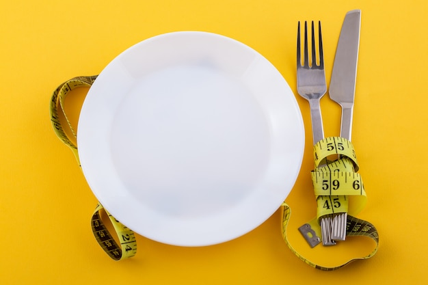 Posate e un piatto bianco con nastro di misurazione su un giallo, il concetto di perdita di peso e dieta